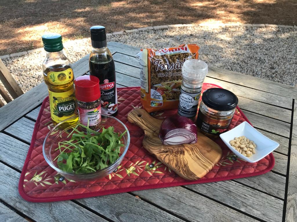 Zutaten auf einem Holztisch unter Pinien: Olivenöl, Crema di Balsamico, Salz, Pfeffermühle, Nudeln, Tomaten, Rucola, Pinienkerne